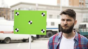 A guy on a picket with a blank label for your title with tracking markers. Angry adult young man with a banner in hands go and shouts loudspeaker rally stock footage