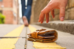 Guy picking up a lost a lost purse/wallet Stock Photos