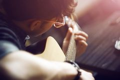 A guy in pink glasses plays a melody on an acoustic guitar. A curly-haired inspired guy in a shirt and pink glasses plays a melody on an acoustic guitar royalty free stock images
