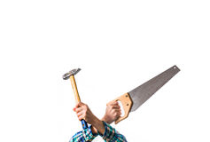 Guy in a plaid red shirt holding a wood saw and a hammer, crosse Royalty Free Stock Image