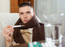 Guy in plaid with thermometer Royalty Free Stock Photography