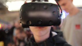 The guy play game in the VR headset virtual reality at a meeting events. The guy plays in the VR headset virtual reality at a meeting events of computer game stock footage