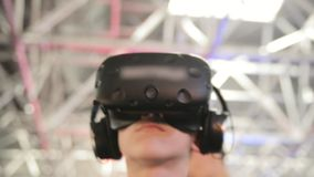The guy play game in the VR headset virtual reality at a meeting events. The guy plays in the VR headset virtual reality at a meeting events of computer game stock video footage