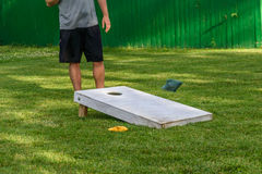 Guy playing bags game in backyard on sunny day. Lower body only of young man in shorts standing by corn hole board outside in sunlight royalty free stock photos
