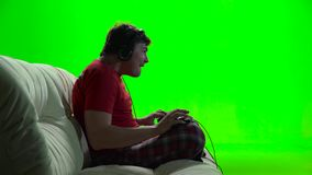 Guy playing computer games sitting on the sofa. Green screen. Guy playing computer games sitting on the sofa sideways to the viewer, shadow of the monitor, head stock video