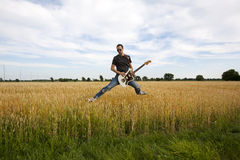 Guy Playing Electric Guitar In Wheat Field Royalty Free Stock Photography