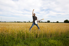 Guy Playing Electric Guitar In Wheat Field Stock Photography