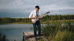 The guy playing the guitar on the dock of the lake. Cool beautiful shots of a musician in nature stock footage