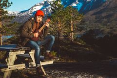Guy playing guitar sitting on a wooden table against the background of mountains, forests and lakes, wear a shirt and a stock images