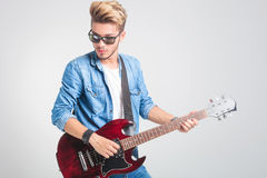 Guy playing guitar in studio while wearing sunglasses Stock Images