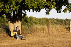 Guy Playing Guitar at Sunset under Maple Tree Royalty Free Stock Image