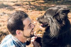 Guy playing with his dog on the field stock image