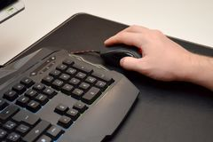 Guy is playing a video game. Close up of a hand lying on a mouse and a black gaming keyboard on a black table. Side view stock images