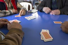 4 guy plays card game on the blue table stock photo