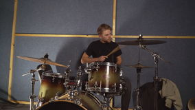 Guy plays on drums kit. Young drummer enjoy repetition in garage. Happy musician playing on drum set and hi hat. Handsome caucasian man wearing in casual black stock video footage