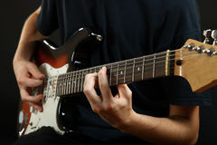 Guy plays the electric guitar. The guy plays the electric guitar on a black background stock images