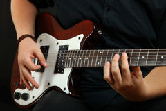 Guy plays the electric guitar. The guy plays the electric guitar on a black background royalty free stock photos