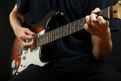 Guy plays the electric guitar. The guy plays the electric guitar on a black background stock photography