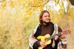 Guy plays emotionally on guitar in autumn forest. A guy with a rug on his shoulders plays emotionally on a guitar in an autumn forest in a blurred background stock photography