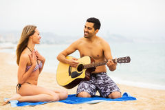 Guy plays guitar for girlfriend Royalty Free Stock Images