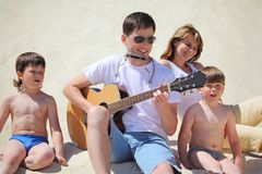 Guy plays guitar and lip accordion with children stock photography