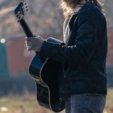 Guy plays guitar in park. A blonde long hair guy plays guitar on a cold autumn morning in park with gloves stock images