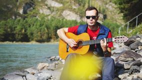 Guy plays on a guitar sings song sitting by mountain river on sunny day Stock Images