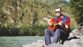 Young cheerful man wearing sunglasses plays on a guitar sings song sits next to mountain river on sunny day. Guy plays on a guitar sitting by mountain river Stock Photo
