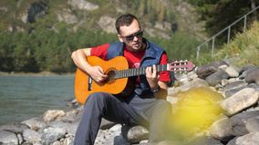 Guy plays on a guitar sitting sings song by mountain river on sunny day on blurred flower at foreground. Guy plays on a guitar sitting by mountain river Stock Photos