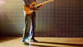 Guy Plays Guitar in Studio onttrekt Hielen bij Helder Licht stock footage
