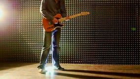 Guy Plays Guitar in Studio onttrekt Hielen bij Helder Licht stock videobeelden