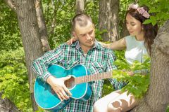 The guy plays  guitar to his girlfriend. romantic meeting. girl sitting in a tree. The guy plays the guitar to his girlfriend. romantic meeting. girl sitting in royalty free stock photo