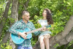 The guy plays his beloved guitar. girl with pleasure with closed eyes listen sitting on a tree stock photo