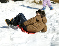 Guy plays with sledding on snow Stock Photo