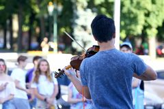 Guy plays violin for street people. The a guy plays violin for street people royalty free stock image