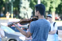 Guy plays violin for street people. The guy plays violin for street people stock images