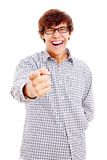 Guy pointing out and laughing. Smiling latin young man showing forefinger on something and laughing very much. Isolated on white background, mask included Royalty Free Stock Photo