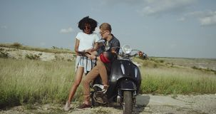 Guy pointing to a map and helping lost girl find her way with a retro 80s motorcycle. Guy pointing to a map and helping lost girl find her way with a retro 80s stock video footage