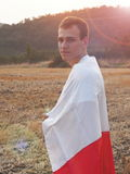 Guy With Polish Flag. Proud polish young man dressed in the flag royalty free stock image
