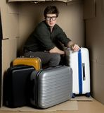 Guy is posing in cramped carton room with his luggage. Travel concept. Full length portrait of serious young man is sitting with bags ine small cardboard box. He royalty free stock photo