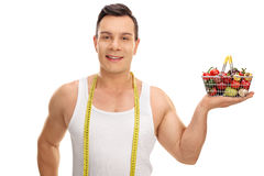 Guy posing with measuring tape and shopping basket Royalty Free Stock Photos