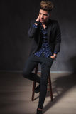 Guy posing seated on stool looking away, in dark studio Royalty Free Stock Photos