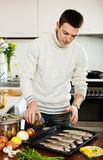 Guy pouring oil in raw fish on roasting pan Stock Image