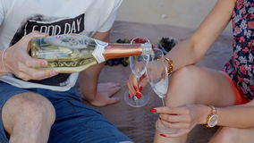Guy pours the girl a glass of champagne stock video