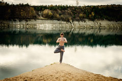Guy practices asanas on yoga in harmony with nature Royalty Free Stock Images
