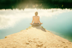 Guy practices asanas on yoga in harmony with nature Stock Image