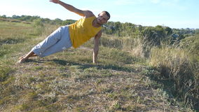 Guy practicing yoga moves and positions outdoors. Young man standing at yoga pose at nature. Athlete doing strength stock video footage