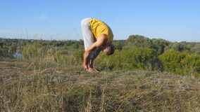 Guy practicing yoga moves and positions outdoors. Young man standing at yoga pose at nature. Athlete doing strength stock video