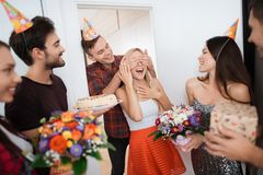 The guy prepared a surprise for the girl`s birthday. He closed her eyes by hands. The guy smiles and leads the girl to a. Surprise. Guests are standing around stock images