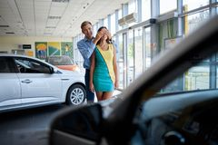 Guy prepared a surprise for his girlfriend. Buying a new car. Happy young couple looking at new car in showroom. The concept of buying a new car Stock Image